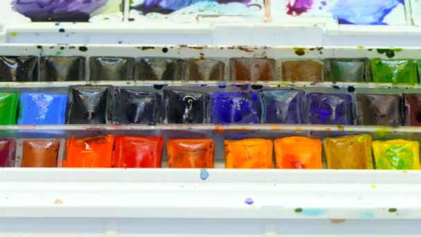 Hand taucht einen Pinsel in der Palette des Aquarells