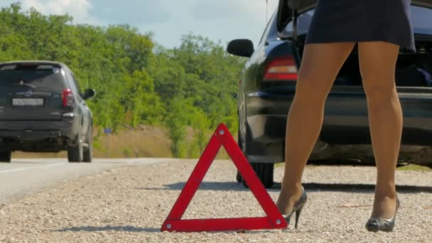 female legs in heels walk against the warning triangle