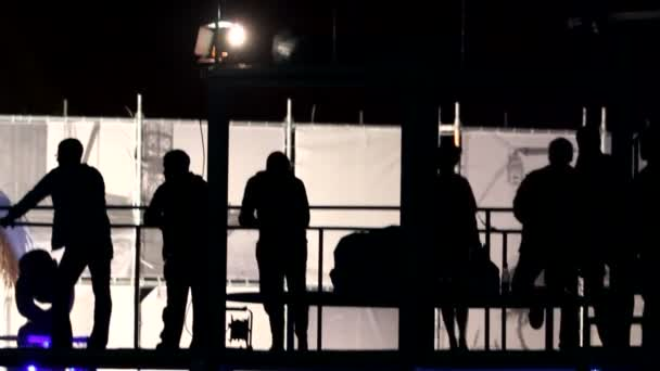 Silhouettes of several people dancing on the balcony