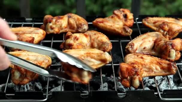 csirke szárnyak grill, férfi segítségével fém fogó, hogy fordult néhány fűszeres csirke szárnyak, amelyeket jelenleg grillezett a barbecue.
