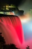 Niagara Falls lit at night show by colorful lights. USA