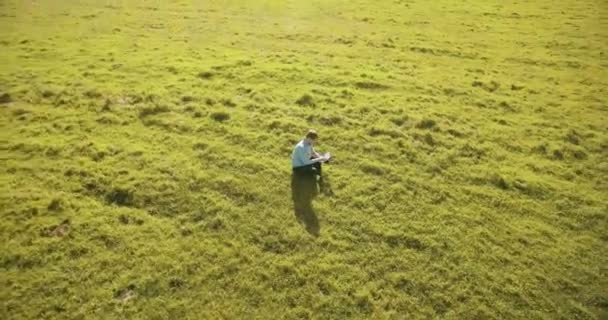 UHD 4k aerial view. Low orbital flight over businessman sitting on green grass with notebook pad at field