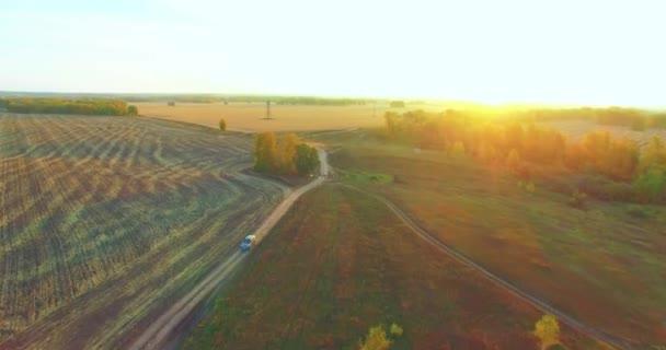 Letecký pohled UHD 4K. Vzdušný let nad žlutým venkovským polem a polní cestou
