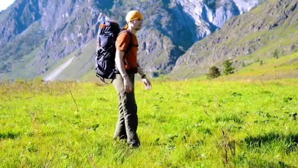 Hiking man walking on green mountain meadow with backpack. Summer sport and recreation concept.