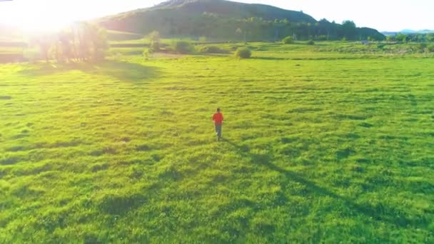 Flight over sport man at perfect green grass meadow. Sunset in mountain