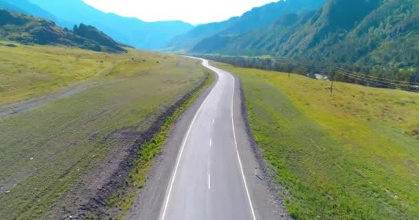 Letecký pohled na rozlišení 4k. Nízký let nad asfalt silnice v horách a pastviny na ráno. Poblíž zelených stromů. Rychlé horizontální pohyb s paprsky slunce.