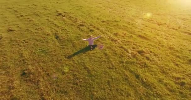 Low orbital flight around man on green grass with notebook pad at yellow rural field.