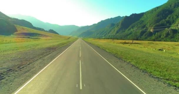 Letecký nízko nad horskou silnicí a loukou za slunečného letního rána.