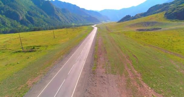 Let přes horskou asfaltovou silnici a louku