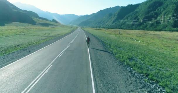 Let nad stopaře turistické chůze po asfaltové silnici. Obrovské venkovských údolí v letním dni. Batoh turistika chlap.