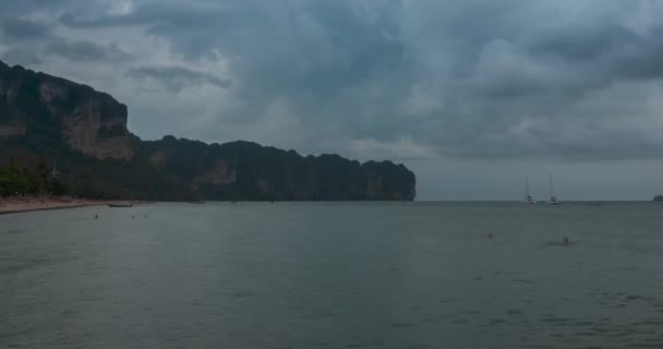 Time lapse of rain clouds over beach and sea landscape with boats. Tropical storm in ocean.