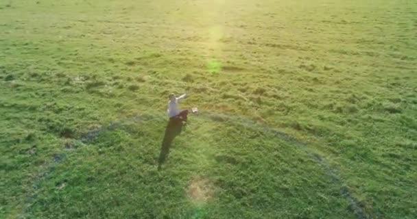 Nízká orbitální let kolem člověka na zelené trávě s poznámkovým blokem na žlutém venkovském poli.