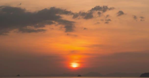 Napnyugtakor fénysugarak csapnak le a tengerre vagy az óceánra. Meleg nyári időjárás a trópusokon. Panoráma mozgás.
