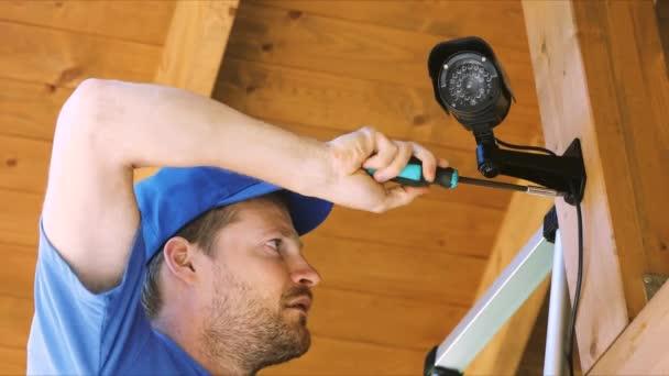 Videotechniker installiert Überwachungskamera im Carport des Hauses