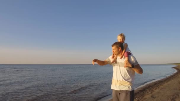 father daughter shoulders walking beach sunset vídeo de stock