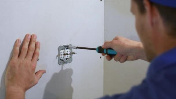 elettricista che installa la presa elettrica sulla parete