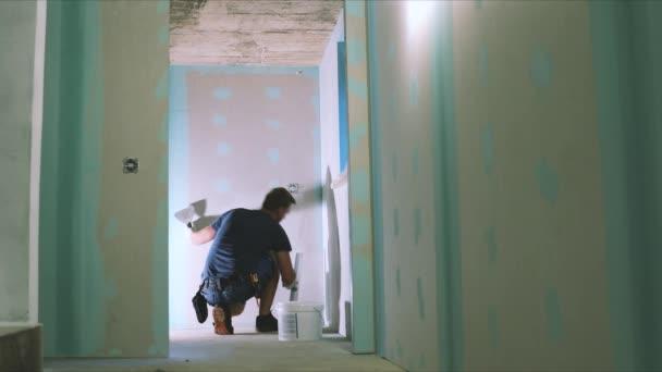 construction worker plastering plasterboard wall