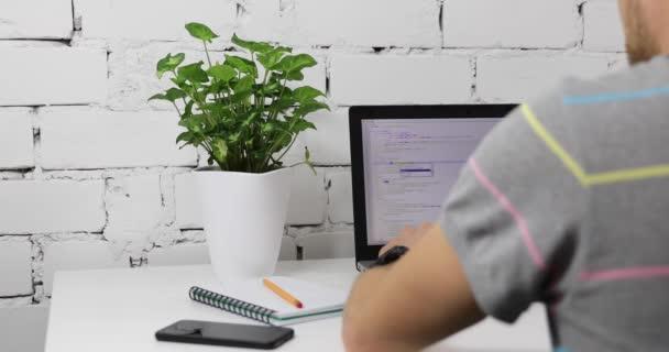 programátor programování web na notebooku ve světlé kanceláři
