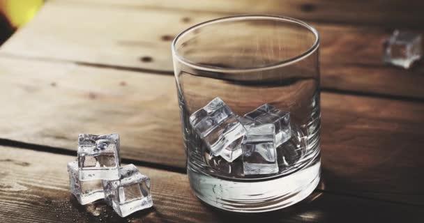 nalil whisky z láhve do sklenice s kostkami ledu