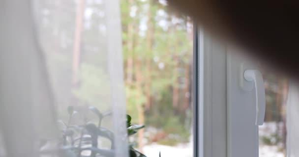 Hand zu öffnen, die Vorhänge und weiße Kunststoff-Fenster zu Hause