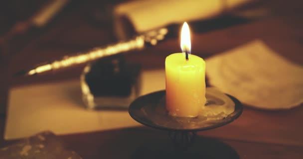 penna piuma retrò e oggetti vintage sul tavolo a lume di candela