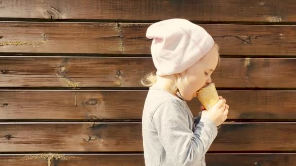 child with ice cream in hand on wooden background