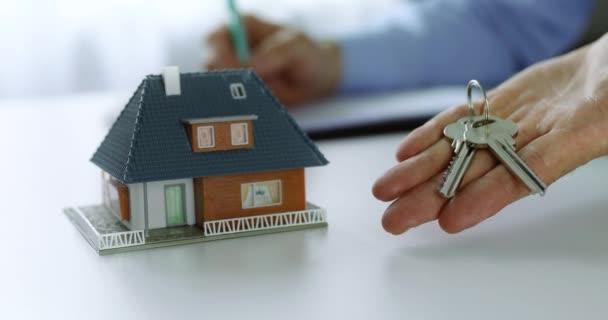 realitní agentka s novými klíči rodinného domu v kanceláři