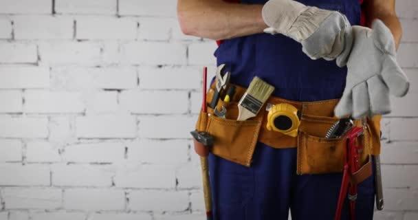 stavební pracovník s nástrojem s pásem na bílé cihlové stěně prostor pro kopírování pozadí