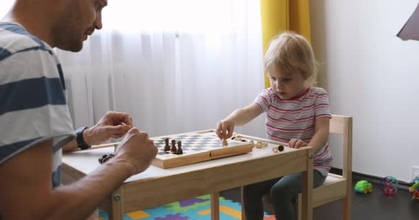 father and daughter spending time together and playing chess