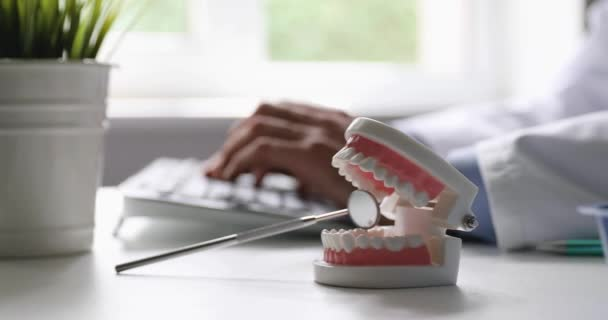 dentist working in dental clinics office typing on computer keyboard focus on tooth model