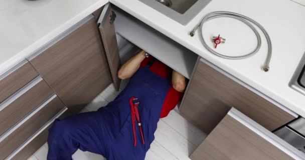 instalatérské služby-instalatér pracující v domácí kuchyni, oprava potrubí dřezu