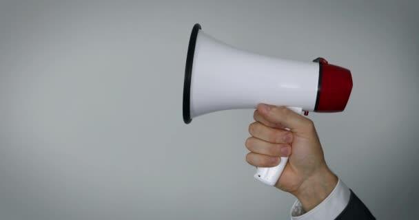 ruka s megafonem na šedém pozadí s prostorem kopírování
