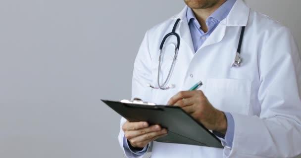 Arzt im weißen Mantel schreibt Dokumente auf Klemmbrett auf grauem Hintergrund