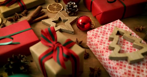 wrapped christmas gifts and decorations on wooden plank background. dolly shot