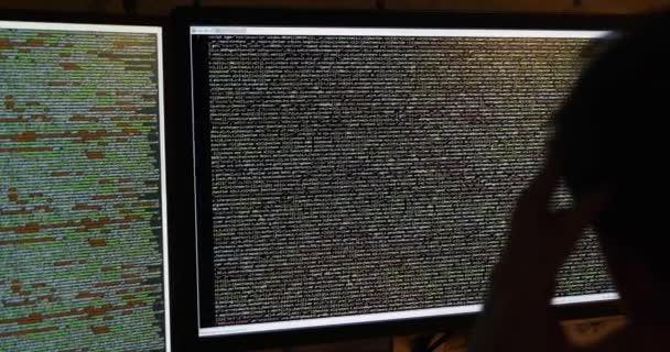 programátor pracující v temné místnosti. posouvání kódu na obrazovce počítače
