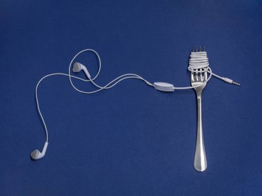 Studio shot of earphones wrapped around a fork against a blue background
