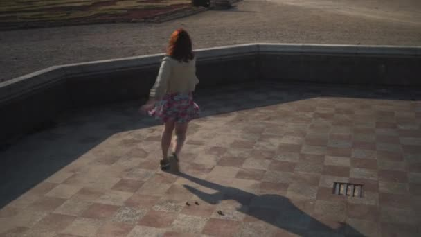 Crazy happy young girl dancing in an empty palace fountain wearing biege jacket and colorful vivid skirt - Ballerina running around