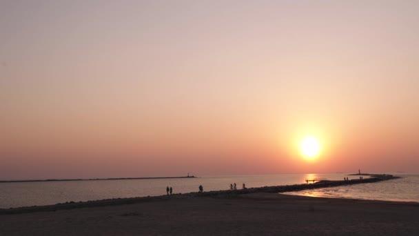 Maják v poslední minutě západu slunce s velkým sluncem v blízkosti obzoru a čirou oblohou