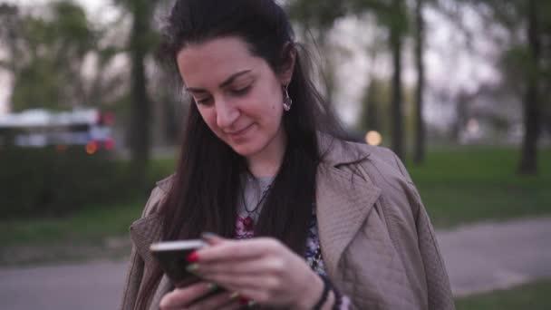 junge Frau benutzt ihr Handy mit Sakura-Blüte im Hintergrund - Lifestyle