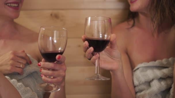 zwei schöne heiße sexy Freundinnen, die Rotwein aus Gläsern trinken und in der finnischen Holzsauna nass vom Dampf plaudern - lachen und lächeln