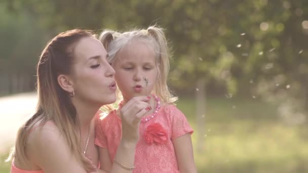 Blowing dandelion - Happy mother playing with her little baby girl daughter and having fun - Young caucasian white mom wearing summer bright vivid color dress - Happinness family concept