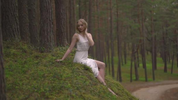 Krásná mladá Blondýnka, která sedí v lesní nymfy v bílých šatech ve stálezelených dřevě