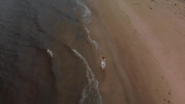 Aerial top view - Beautiful young blonde woman walking along the sea on a beach nymph in white dress near sea with waves during a dull gloomy weather with stormy wind and rain