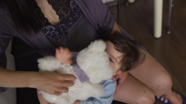 Matka si zahrává s medvídkem a jejím dětským synem v interiérech v asijském smíšené etnické příslušnosti chlapec s modrou tělíčkou s úsměvem na těle těhotná