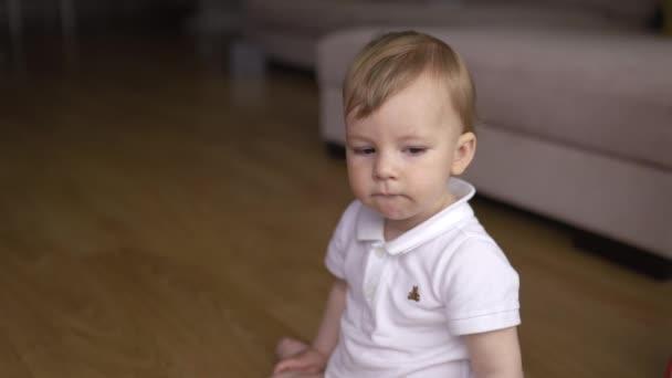Chlapeček sedí na podlaze v rodinném domě v bytě ospalého a zvědavé-dítě nosí bílé tričko