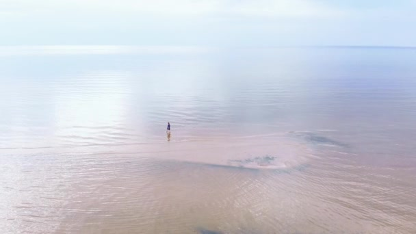 Aerial: Young woman in blue bright dress walking around - Shallow water scenic yellowish sunset landscape at the Baltic Sea - Drone flying view from above