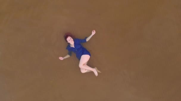 Aerial: Young woman in blue bright dress laying down - Shallow water scenic yellowish sunset landscape at the Baltic Sea - Drone flying view from above