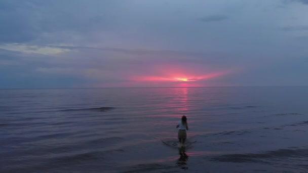 Antenne: junge Frau im Rock spaziert am Strand entlang und genießt das Leben und die Natur weit im Hintergrund - Drohnenflug von oben