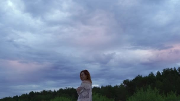 Young woman girl in a white dress standing in the foreground and enjoying rare glowing nature sky - Moody cold sunset with vivid magenta bluish colors at the Baltic Sea Gulf in summer