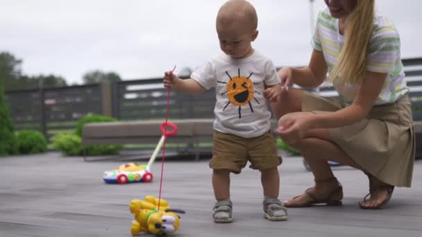Mladá matka si hraje a baví se se svým chlapím synem v zahradě s hračkama-rodinné hodnoty teplé barevné letní scény